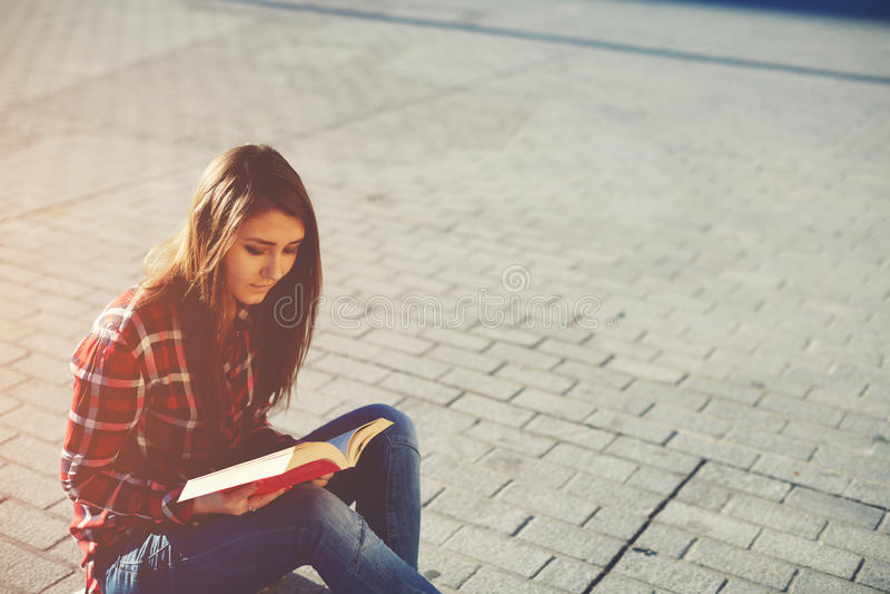 Привлекательная маленькая девочка наслаждаясь хорошей книгой стоковое изображение