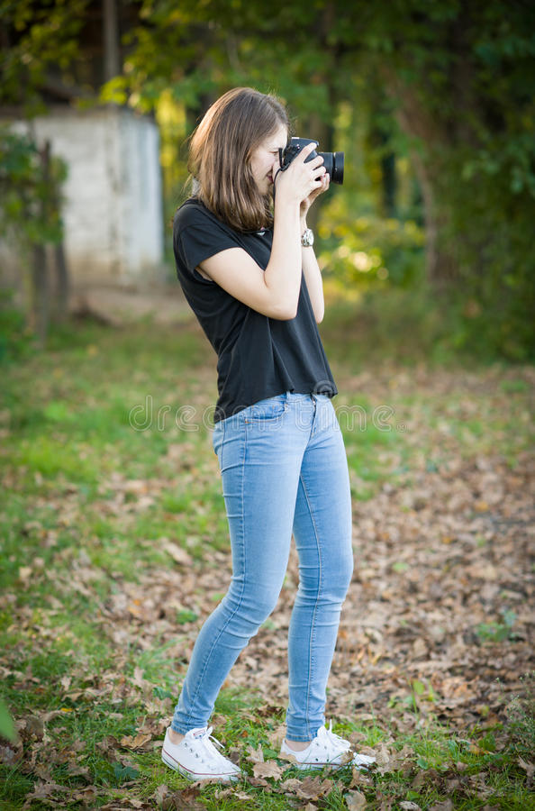 Привлекательная маленькая девочка фотографируя outdoors Милый девочка-подросток в голубых джинсах и черной футболке принимая фото стоковое фото rf