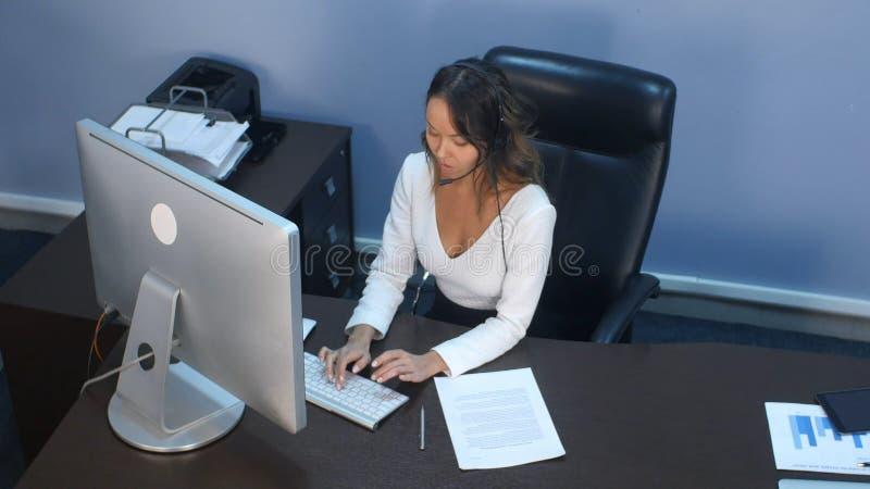 Привлекательная молодая азиатская женщина работая в центре телефонного обслуживания стоковое изображение