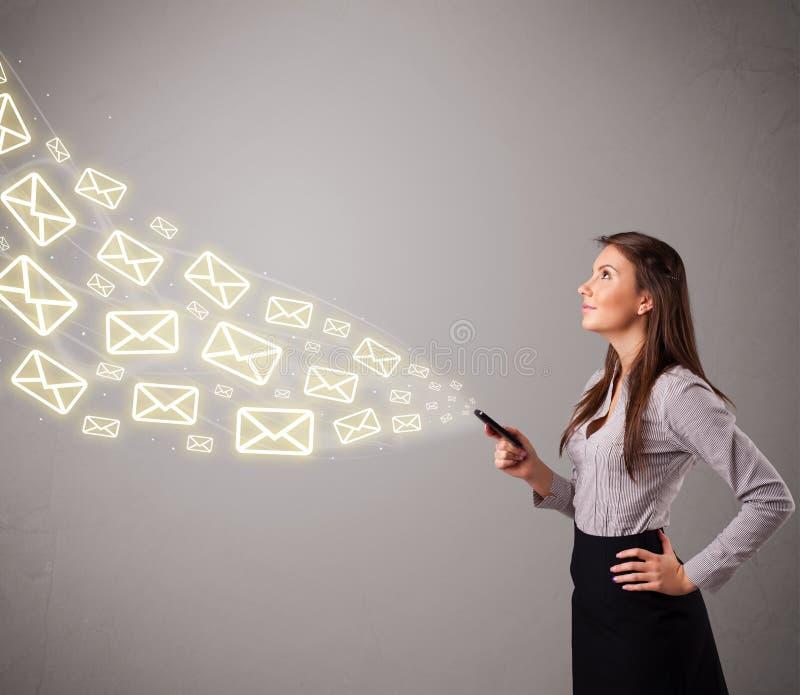 Привлекательная молодая дама держа телефон с значками сообщения стоковое изображение