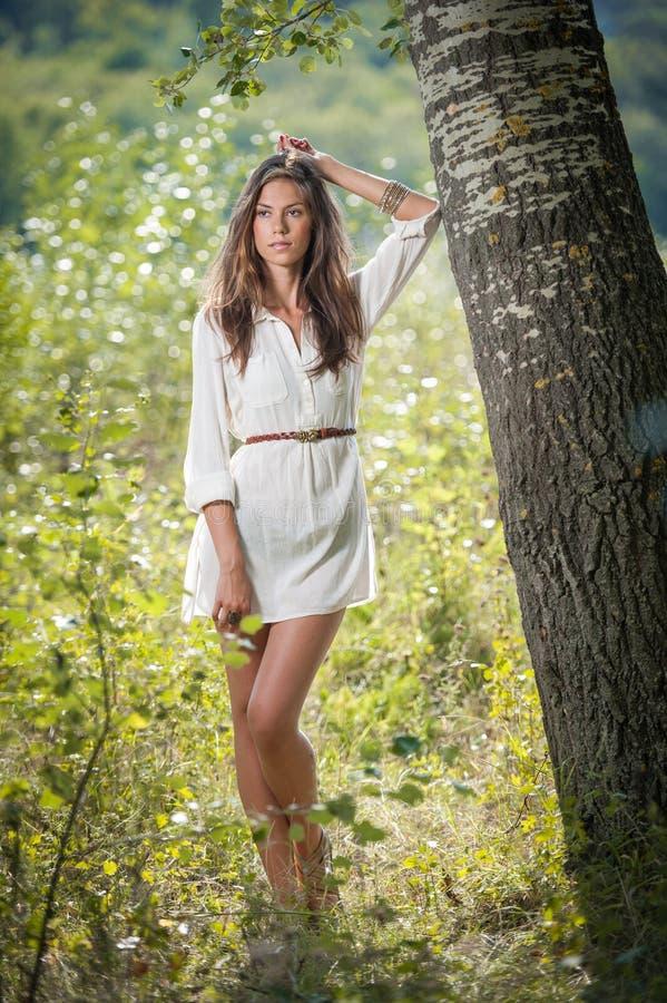 Привлекательная молодая женщина в белом коротком платье представляя около дерева в солнечном летнем дне красивейшая наслаждаясь п стоковая фотография