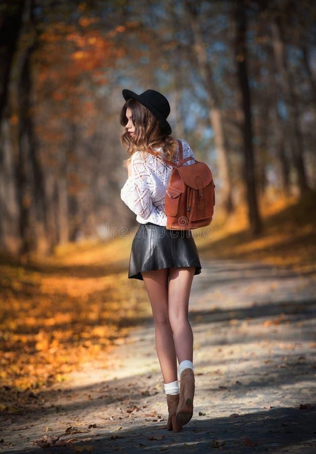 Привлекательная молодая женщина в осенней съемке outdoors Красивая модная девушка школы представляя в парке с увяданными листьями стоковое фото rf