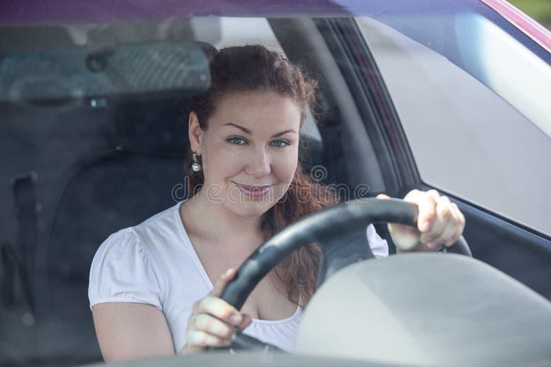 Привлекательная молодая женщина держа рулевое колесо стоковое изображение rf