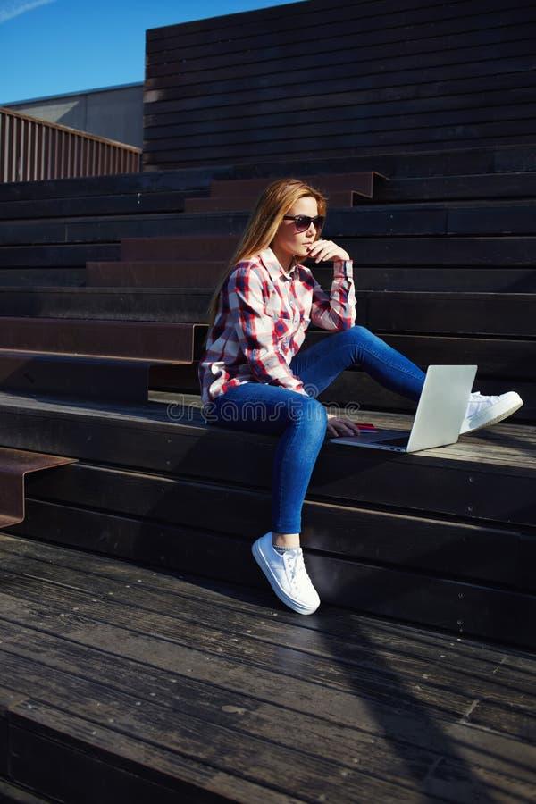 привлекательная молодая женщина используя компьтер-книжку сидя на деревянной лестнице наслаждаясь солнечным днем outdoors стоковые изображения