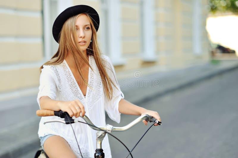 Привлекательная молодая женщина с велосипедом стоковая фотография