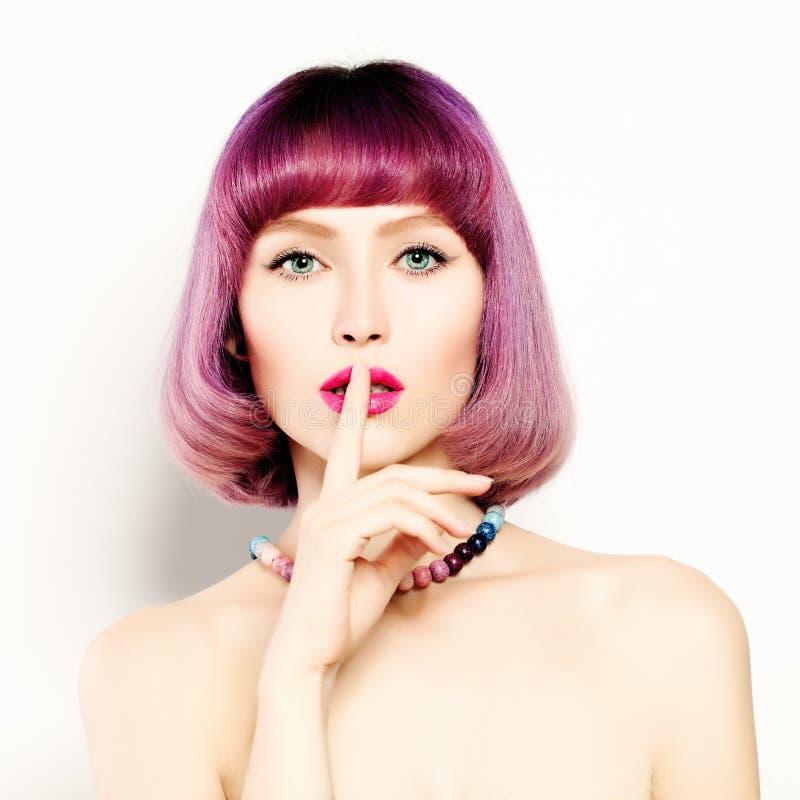 Привлекательная молодая женщина с ее пальцем на ее губах стоковое изображение rf