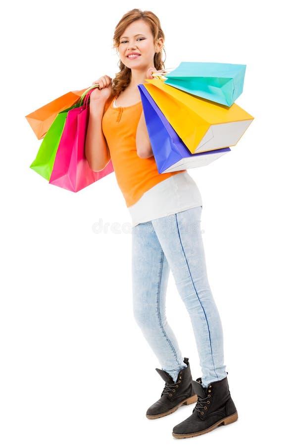 Привлекательная молодая женщина с красочными хозяйственными сумками стоковые фото