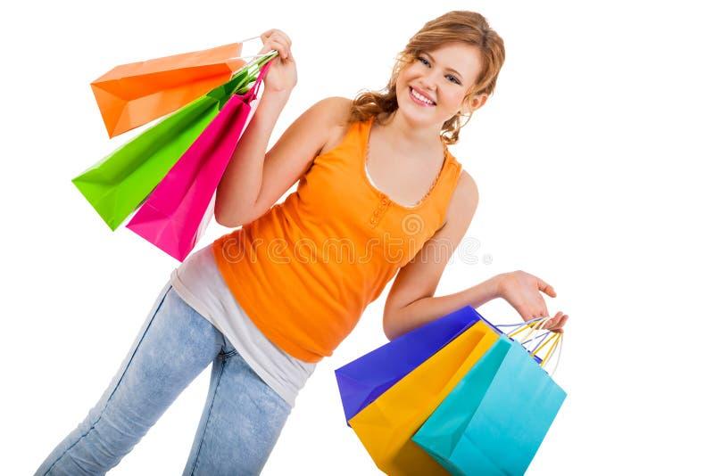 Привлекательная молодая женщина с красочными хозяйственными сумками стоковая фотография