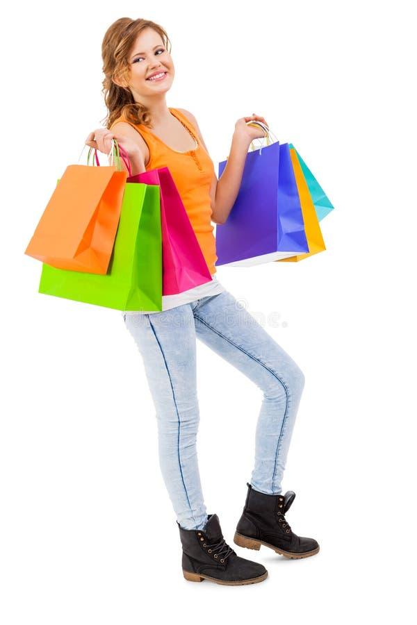 Привлекательная молодая женщина с красочными хозяйственными сумками стоковое изображение rf