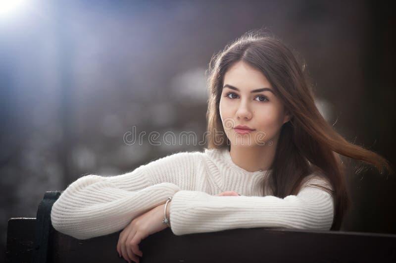 Привлекательная молодая кавказская девушка нося белую блузку сидя на стенде в парке Девушка красивых коричневых волос предназначе стоковая фотография