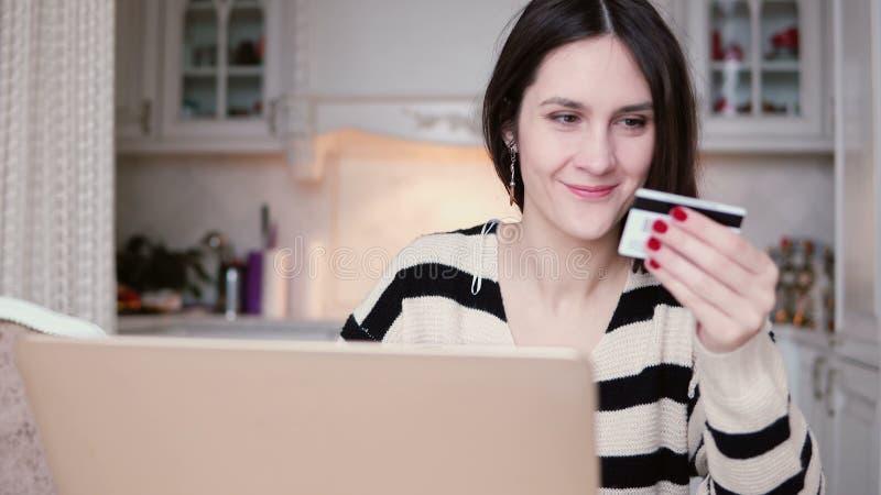 Привлекательная молодая усмехаясь женщина использует пластичный ходить по магазинам кредитной карточки онлайн с компьтер-книжкой  стоковое изображение rf