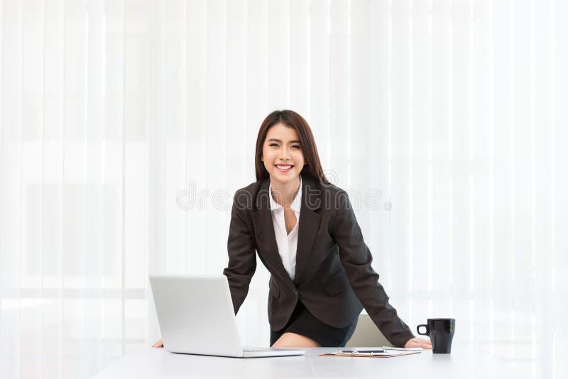Привлекательная молодые коммерсантка и компьтер-книжка работая в офисе стоковая фотография rf