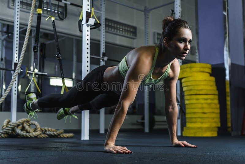 Привлекательная мышечная стойка тренера CrossFit женщины в планке во время разминки стоковое фото