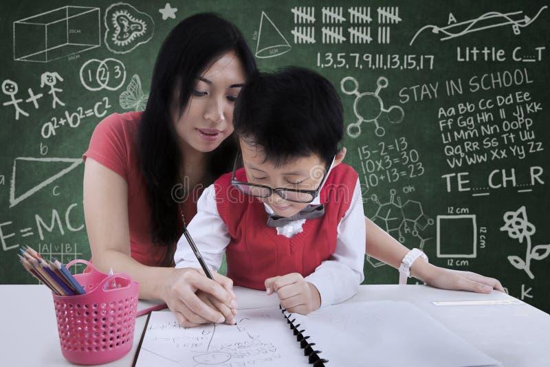 Привлекательная помощь учителя мальчик, который нужно написать в классе стоковое изображение