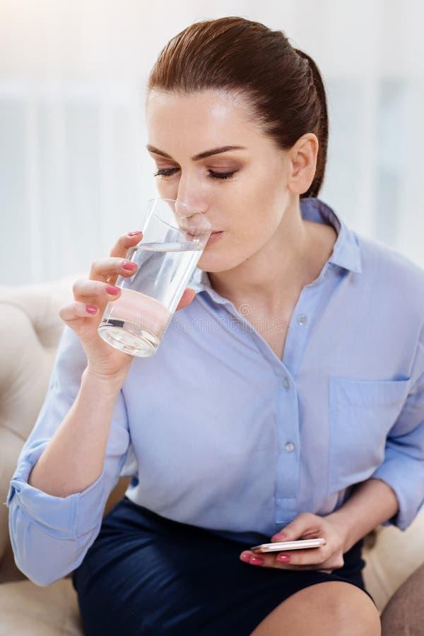 Привлекательная работающий на самого себя женщина имея воду стоковые изображения