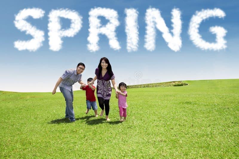 Привлекательная семья бежать в поле стоковое изображение