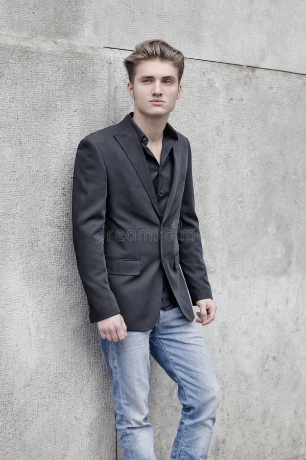 Привлекательная синь наблюдала, белокурая склонность молодого человека против белой стены стоковые фотографии rf