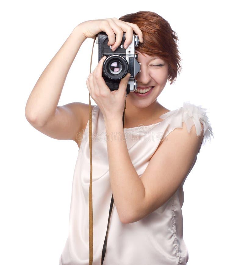 Привлекательная смешная девушка с камерой над белизной стоковая фотография rf