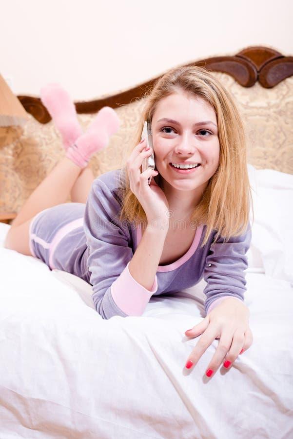 Привлекательная счастливая усмехаясь молодая женщина в кровати в пижамах говоря на усмехаясь передвижной сотового телефона счастл стоковая фотография rf