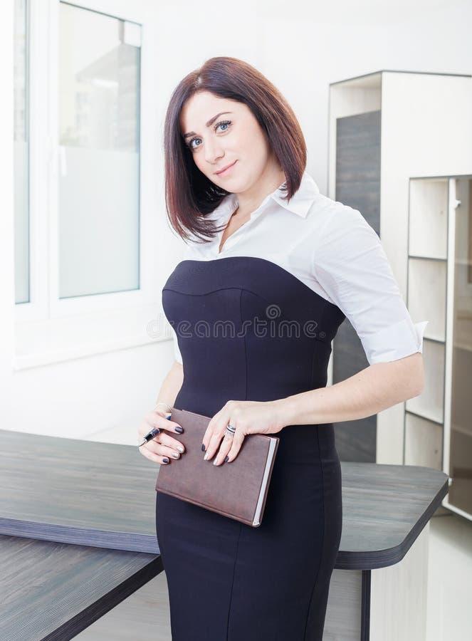 Привлекательная темн-с волосами женщина нося черно-белое платье стоя около таблицы в офисе с тетрадью стоковое изображение