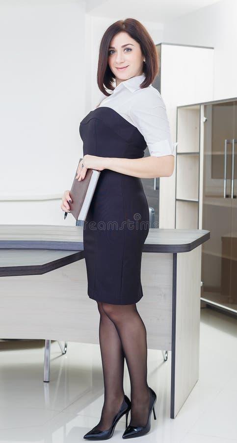 Привлекательная темн-с волосами женщина нося черно-белое платье стоя около таблицы в офисе с тетрадью стоковые фотографии rf