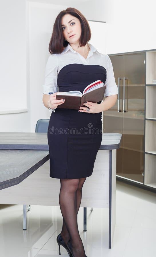 Привлекательная темн-с волосами женщина нося черно-белое платье стоя около таблицы в офисе с тетрадью стоковое фото rf