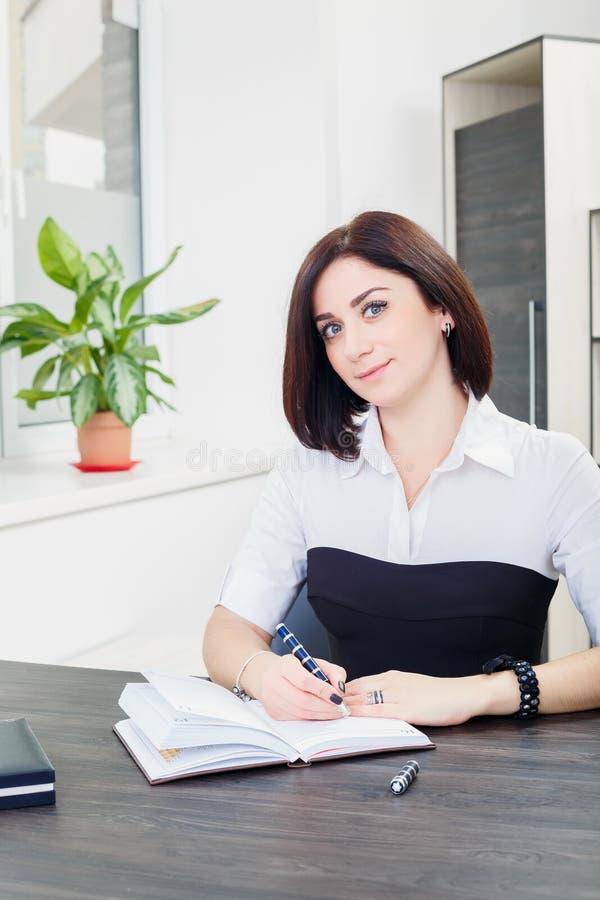 Привлекательная темн-с волосами женщина нося черно-белую блузку сидя на столе в офисе стоковое фото rf
