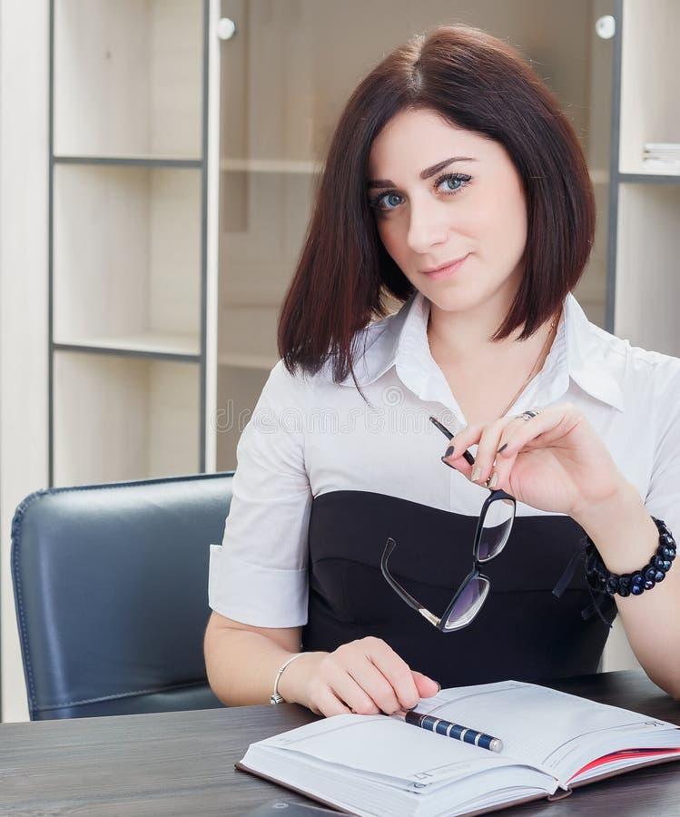 Привлекательная темн-с волосами женщина нося черно-белую блузку сидя на столе в офисе стоковые изображения rf