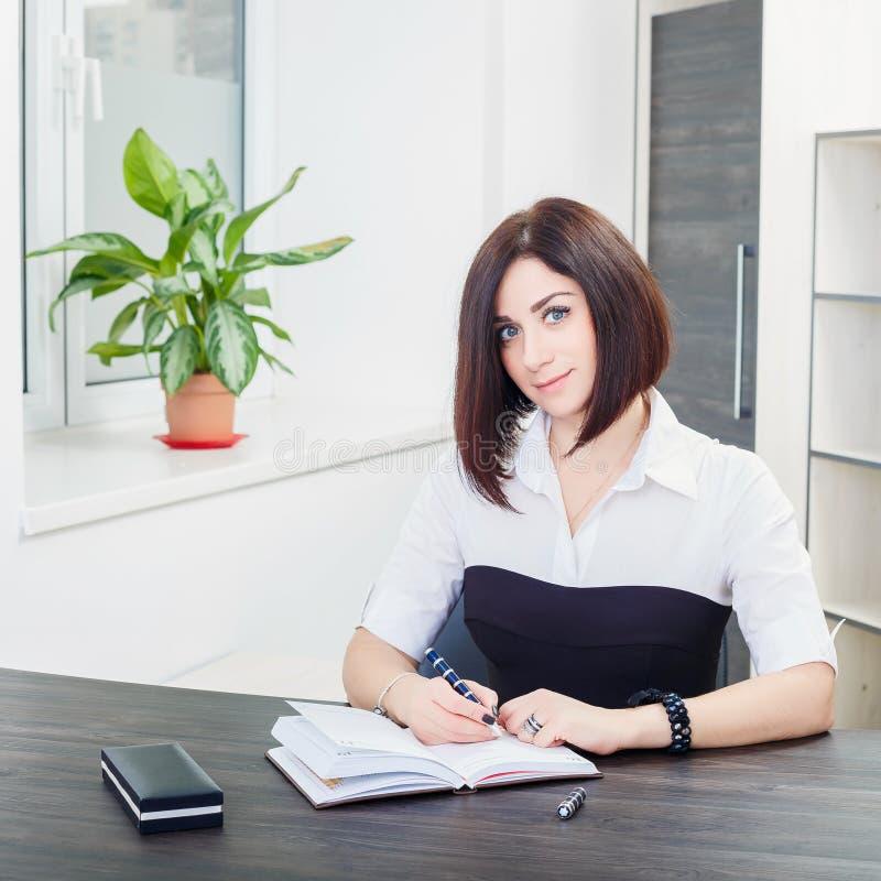 Привлекательная темн-с волосами женщина нося черно-белую блузку сидя на столе в офисе стоковые фото