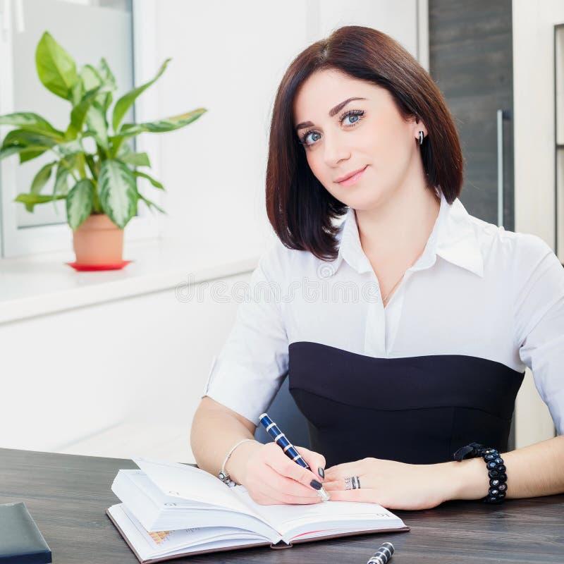 Привлекательная темн-с волосами женщина нося черно-белую блузку сидя на столе в офисе стоковое изображение