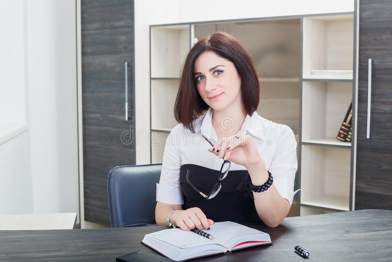 Привлекательная темн-с волосами женщина нося черно-белую блузку сидя на столе в офисе стоковые изображения