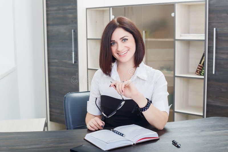 Привлекательная темн-с волосами женщина нося черно-белую блузку сидя на столе в офисе стоковое фото