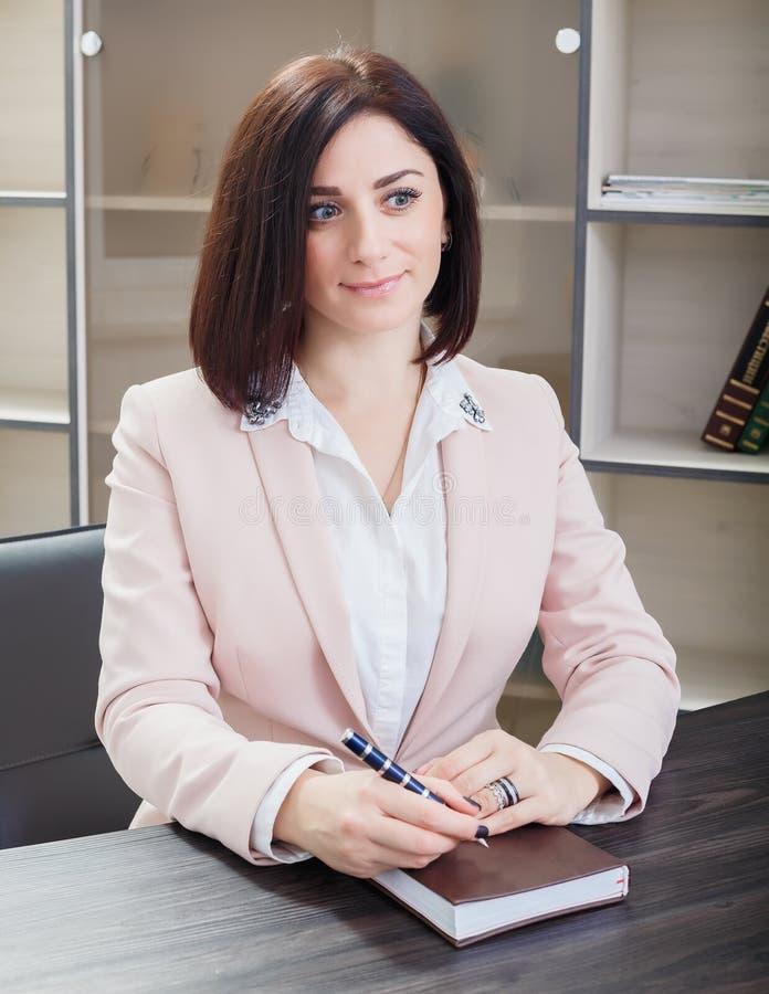 Привлекательная темн-с волосами женщина одела в бежевом костюме сидя на столе в офисе с тетрадью стоковое фото
