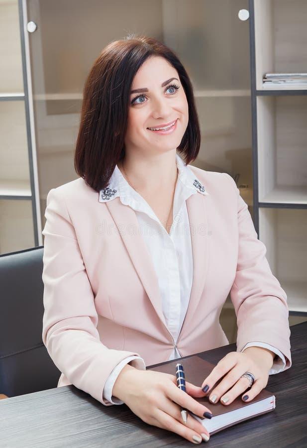 Привлекательная темн-с волосами женщина одела в бежевом костюме сидя на столе в офисе с тетрадью стоковая фотография