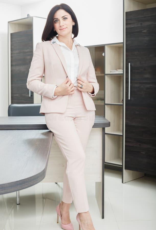 Привлекательная темн-с волосами женщина одела в бежевом костюме стоя около таблицы в офисе стоковые изображения rf