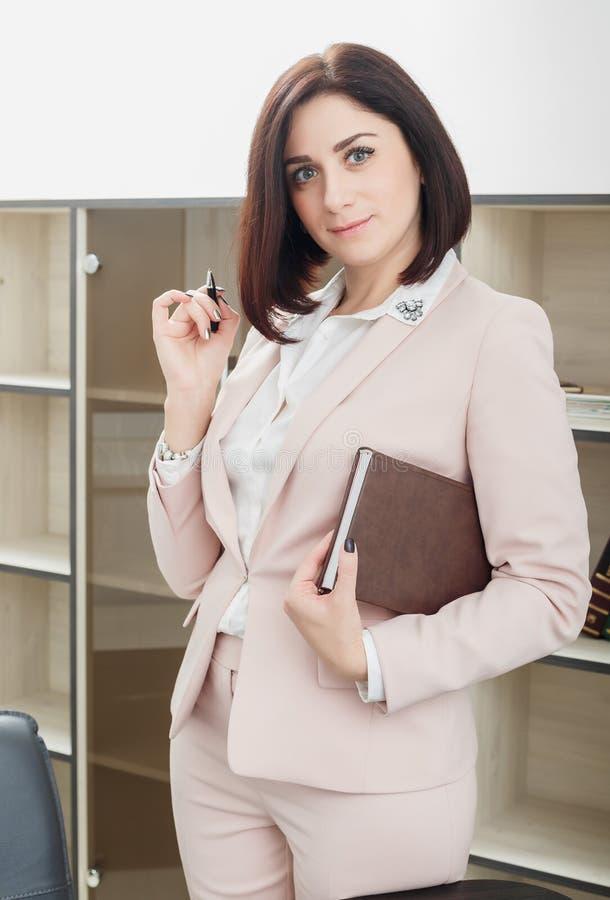 Привлекательная темн-с волосами женщина одела в бежевом костюме стоя около таблицы в офисе и держа тетрадь стоковые изображения rf