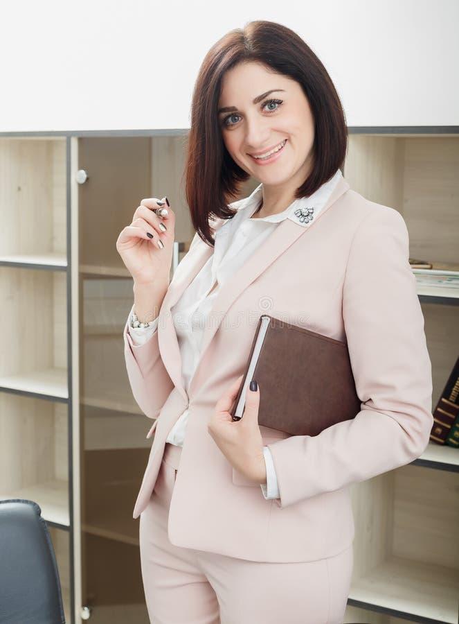 Привлекательная темн-с волосами женщина одела в бежевом костюме стоя около таблицы в офисе и держа тетрадь стоковая фотография rf