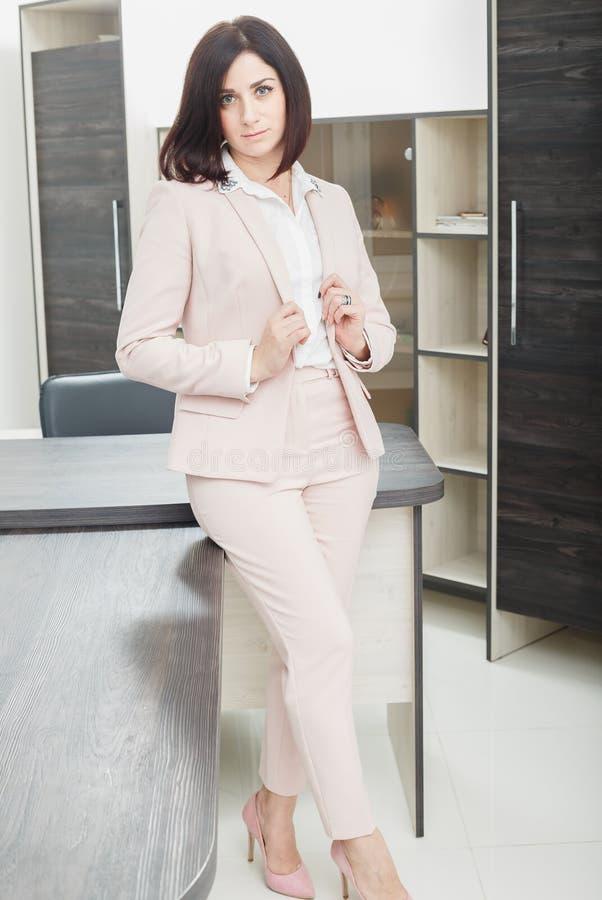 Привлекательная темн-с волосами женщина одела в бежевом костюме стоя около таблицы в офисе стоковая фотография