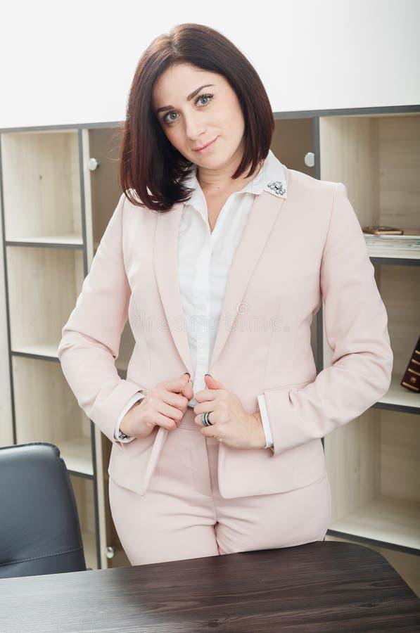 Привлекательная темн-с волосами женщина одела в бежевом костюме стоя около таблицы в офисе стоковая фотография rf