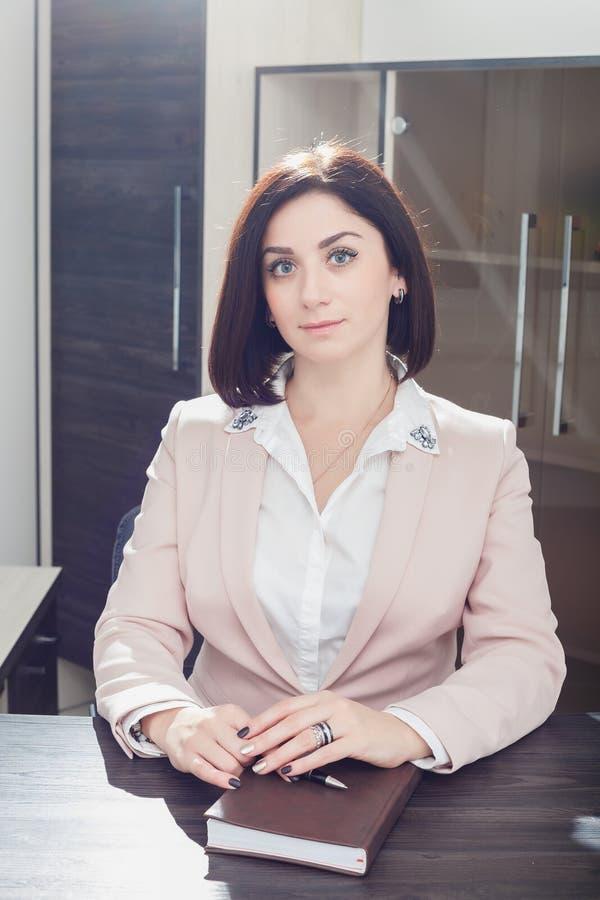 Привлекательная темн-с волосами женщина одела в бежевом idit костюма на таблице в офисе с тетрадью стоковая фотография