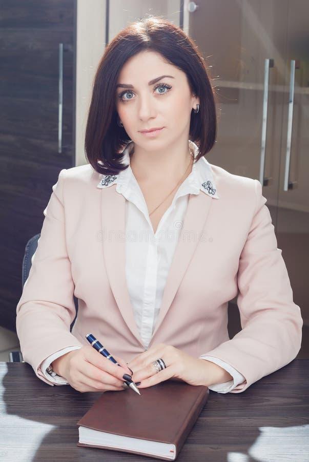 Привлекательная темн-с волосами женщина одела в бежевом idit костюма на таблице в офисе с тетрадью стоковые изображения