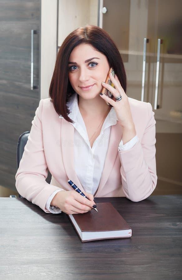 Привлекательная темн-с волосами женщина одела в бежевом idit костюма на таблице в офисе с тетрадью стоковые изображения rf