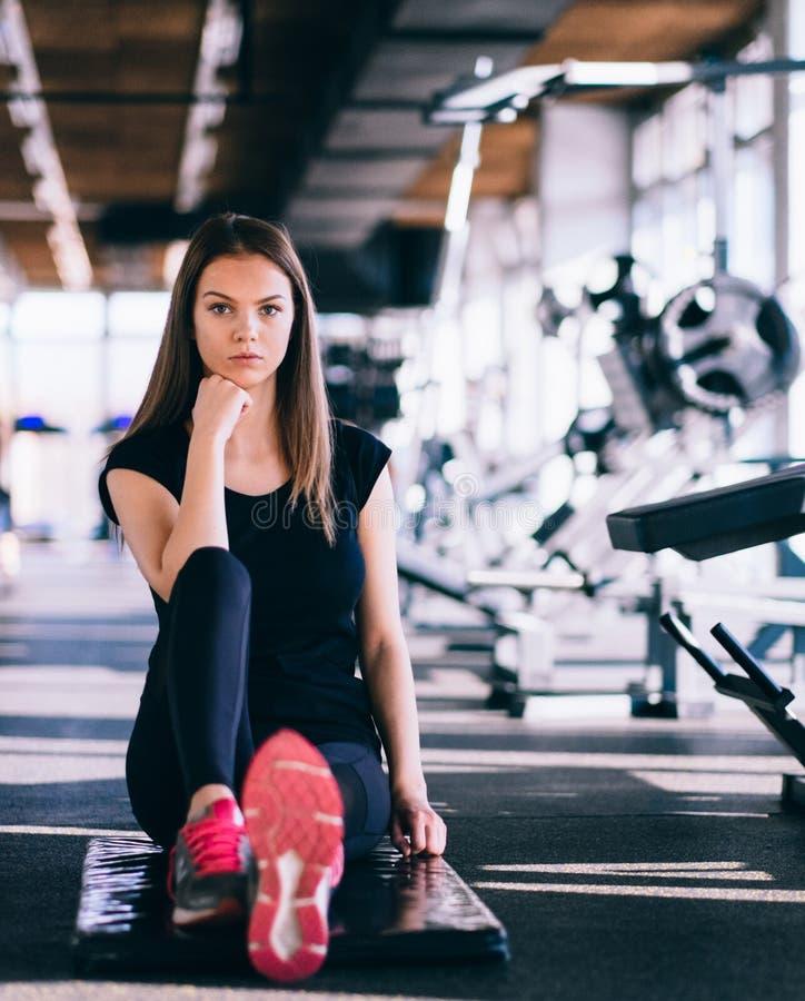 Привлекательная тонкая девушка делая протягивать работает на черной циновке в современном спортзале фитнеса Утомленная девушка ра стоковое фото rf