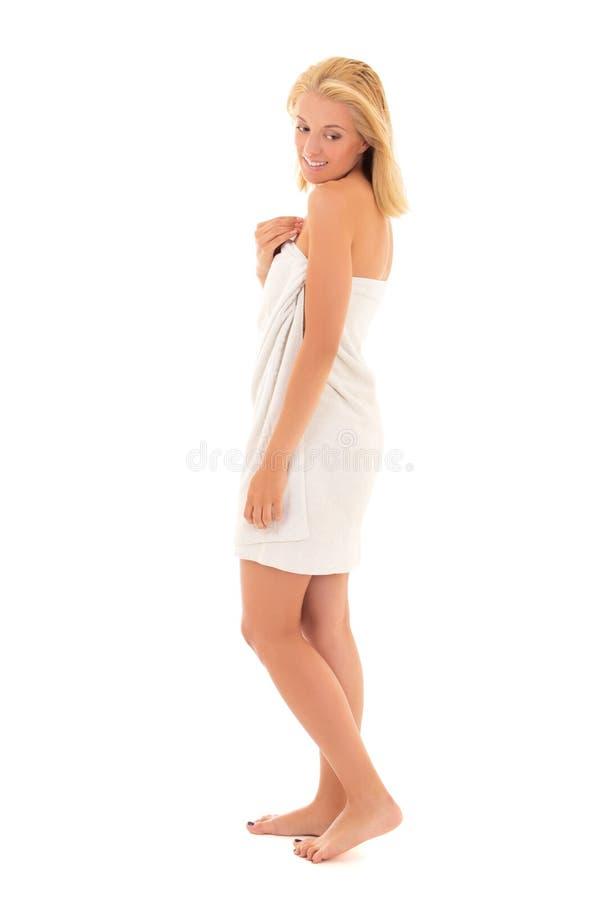 Привлекательная усмехаясь женщина blondie в полотенце представляя над белизной стоковое изображение rf