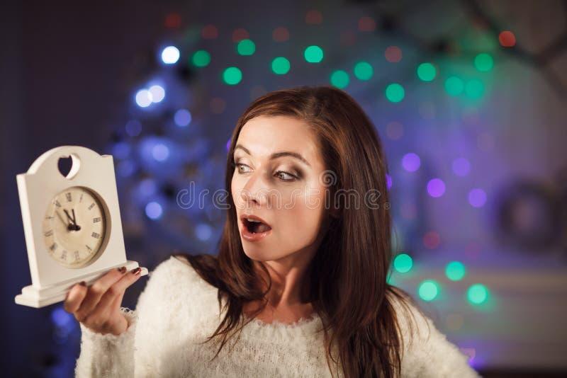 Привлекательная удивленная женщина держа часы около рождественской елки стоковое изображение