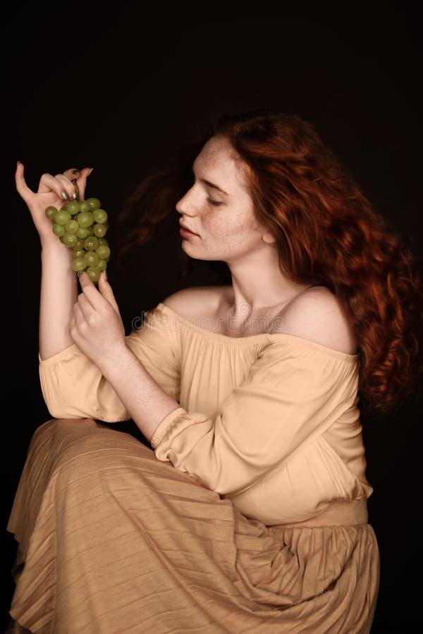 Привлекательная чувственная женщина redhead представляя с зелеными виноградинами стоковое фото