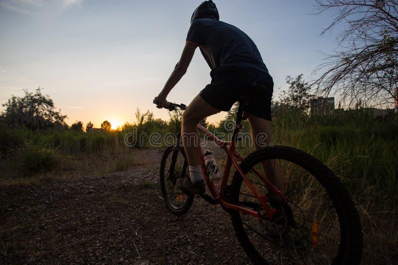 Привлекательная sporty девушка с длинными волосами на велосипеде на заходе солнца стоковые изображения