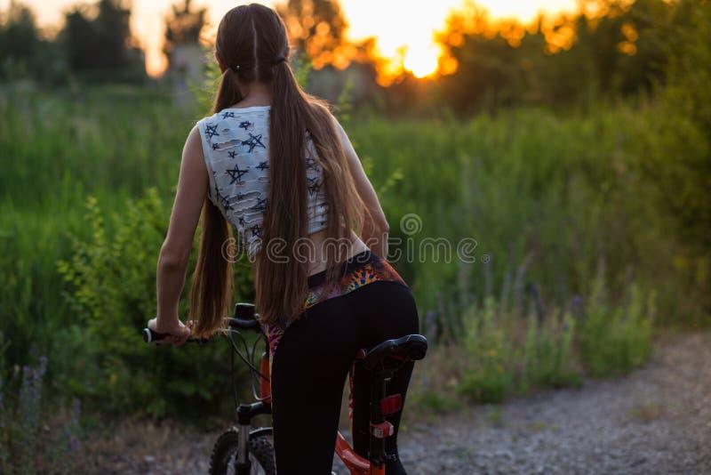 Привлекательная sporty девушка с длинными волосами на велосипеде на заходе солнца стоковая фотография rf