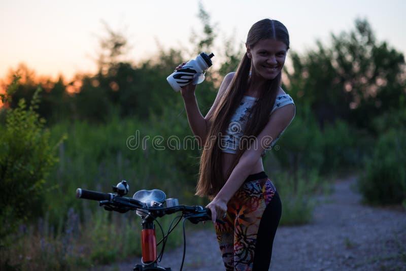 Привлекательная sporty девушка с длинными волосами на питьевой воде велосипеда от бутылки спорта на заходе солнца стоковые изображения