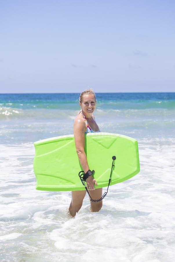 Привлекательное восхождение на борт буг женщины в океанских волнах стоковое фото rf
